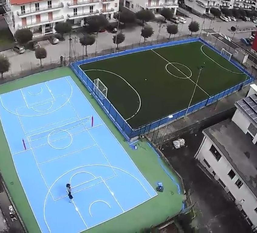 campo polivalente basket e pallavolo in resina e adiacente campo di calcetto in erba sintetica