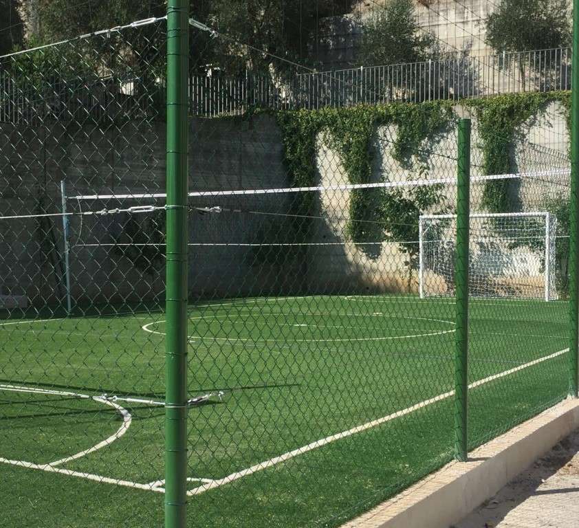 campo polivalente per di calcetto e la pallavolo in erba sintetica completo di reti di recinzione perimetrali